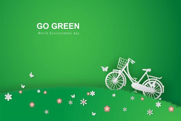 Arte di carta di fondo verde con la bicicletta nel parco del giardino floreale del campo.