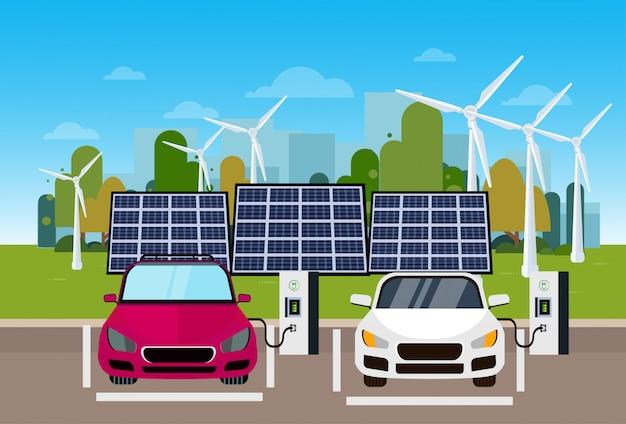 Automobili elettriche che si caricano alla stazione dai pani del vento e dalle batterie del pannello solare concetto ecologico di vechicle