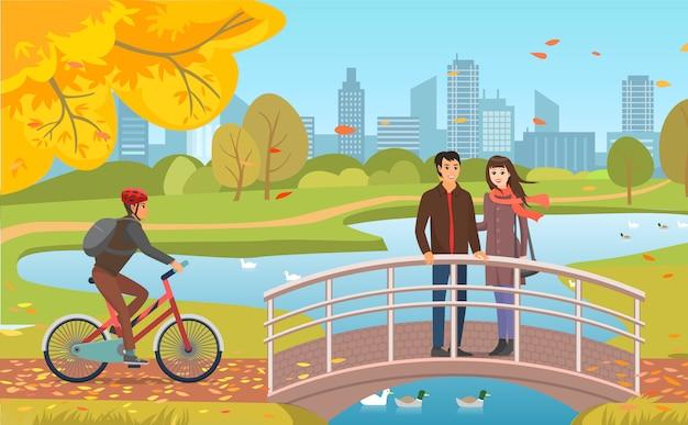 Autumn park con l'illustrazione di guy riding bicycle e delle coppie