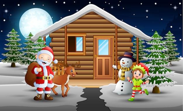 Babbo natale ed elfo in piedi davanti alla casa nevica