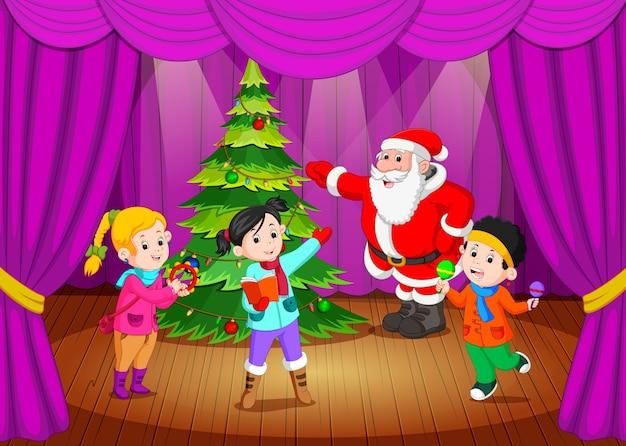 Babbo natale sul palco con bambini che cantano