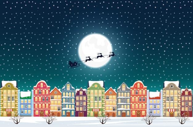 Babbo natale vola sopra un centro storico innevato decorato vicino alla luna alla vigilia di natale.