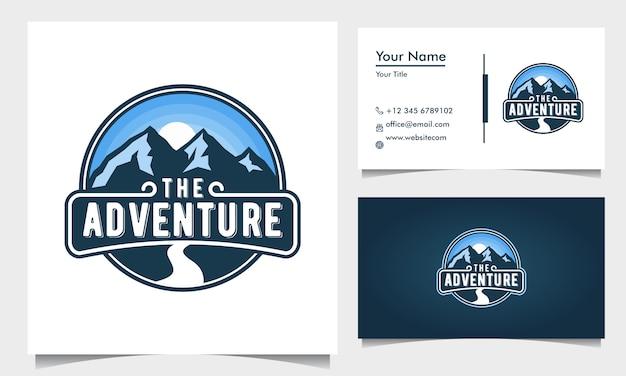 Badge design logo avventura con montagne blu e strada e alba, tramonto con biglietto da visita