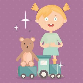 Bambina che gioca con i giocattoli dell'orsacchiotto dell'orso e del treno