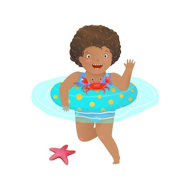 Bambina che gioca con il pesce granchio di mare e la stella nell'oceano nuotando con anello gonfiabile.