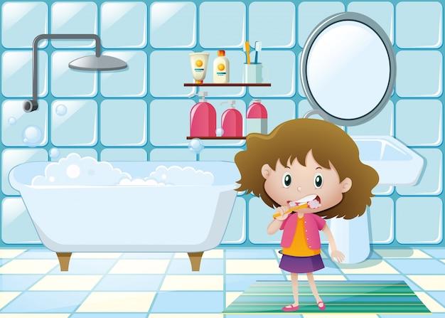 Bambina che spazzola i denti in bagno