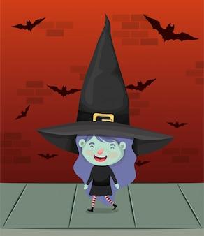 Bambina con il costume da strega nel muro con pipistrelli volanti