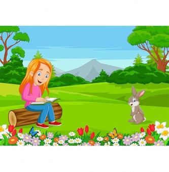 Bambina del fumetto che legge un libro nel parco