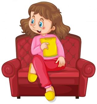 Bambina sul sofà che mangia spuntino su fondo bianco