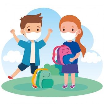 Bambini carini che indossano una maschera medica per prevenire il coronavirus covid 19 con la borsa di scuola