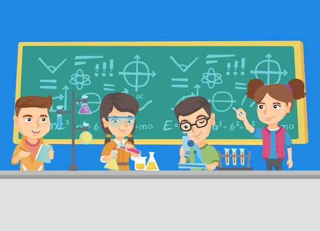 Bambini caucasici che lavorano in classe di chimica.