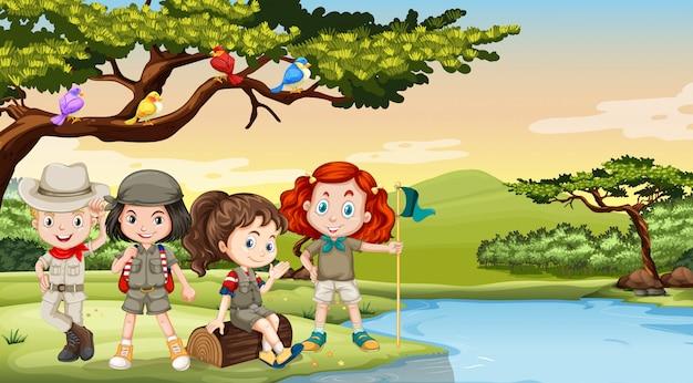Bambini che accampano vicino al fiume