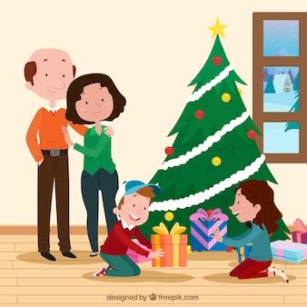 Bambini che disimballano i loro regali di natale con i genitori che guardano