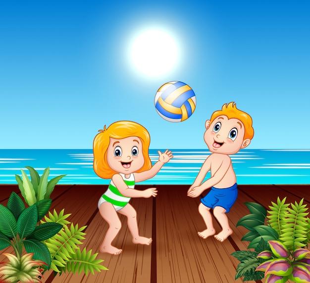 Bambini che giocano a pallavolo sul molo sul mare