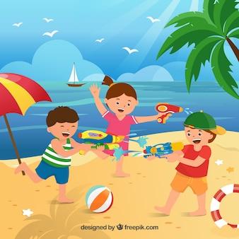Bambini che giocano in spiaggia con pistole ad acqua in plastica