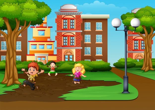 Bambini che giocano una pozza di fango nel parco della città