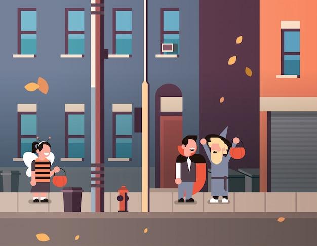 Bambini che indossano mostri ape dracula costumi da mago che camminano sullo sfondo della città