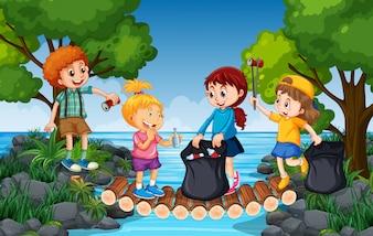 Bambini che raccolgono rifiuti vicino al fiume