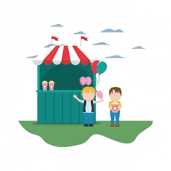 Bambini con negozio di carnevale e popcorn con zucchero filato