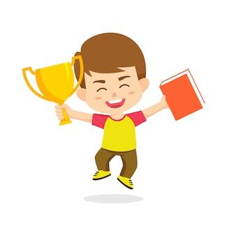 Bambini del ragazzo che saltano tenendo trofeo e libro