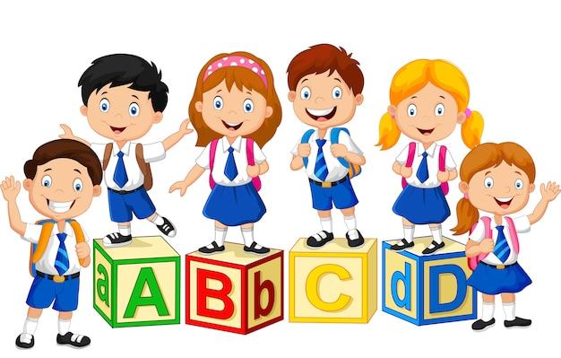 Bambini della scuola felice con blocchi alfabeto