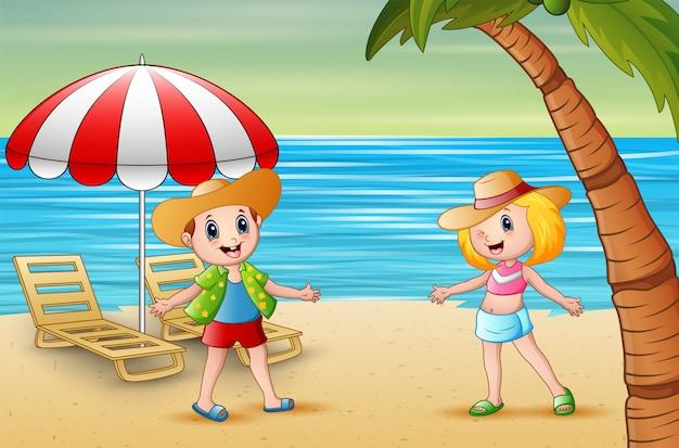 Bambini divertenti sulla spiaggia in un cappello di paglia