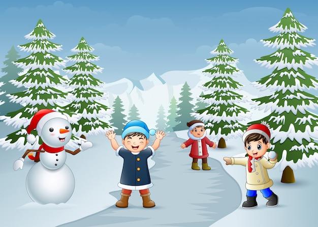 Bambini felici che giocano con un pupazzo di neve in inverno