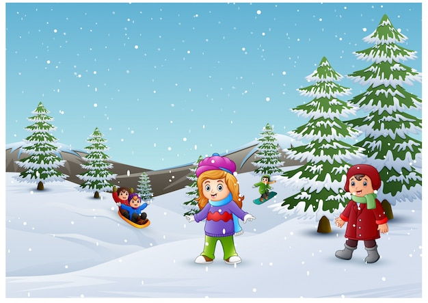 Bambini felici che giocano nel paesaggio invernale