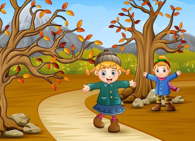 Bambini felici che giocano nel parco in autunno