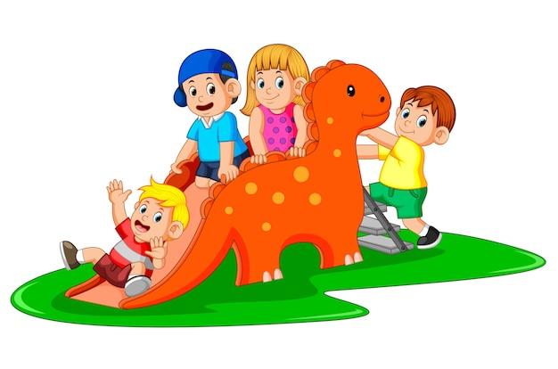 Bambini felici che giocano sullo scivolo dei dinosauri e alcuni di loro salgono la scala