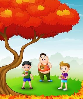 Bambini felici che mangiano negli alberi di autunno