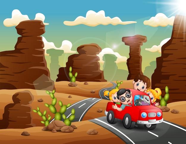 Bambini felici che viaggiano in auto rossa attraverso il deserto