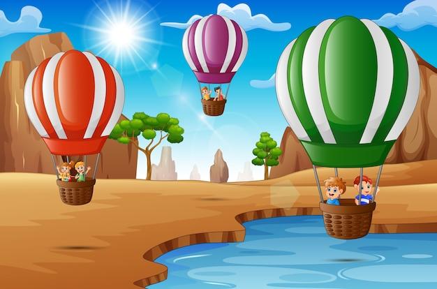 Bambini felici del fumetto che guidano l'aerostato di aria calda nel deserto
