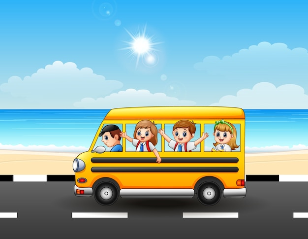Bambini felici della scuola che guidano uno scuolabus sulla via del mare