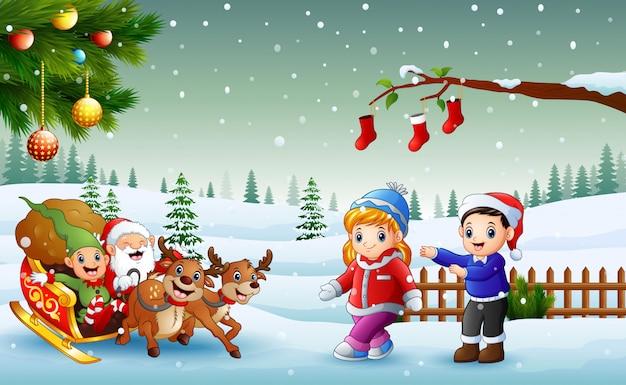 Bambini felici e babbo natale con elfo in sella a una slitta con borsa di regali trainati da reindee
