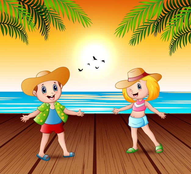 Bambini felici sul molo e guardando un paesaggio tramonto