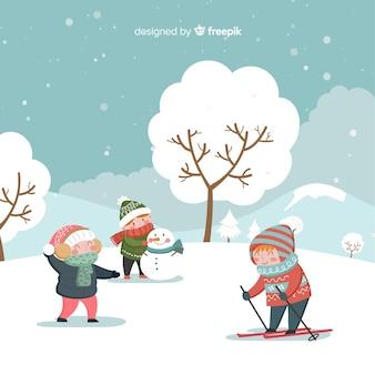 Bambini invernali che giocano sullo sfondo
