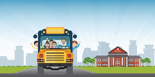 Bambini sorridenti felici che guidano su uno scuolabus giallo con un autista sul fondo di vista dell'edificio scolastico.