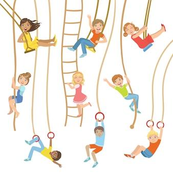 Bambini su altalene e altre attrezzature sportive in corda