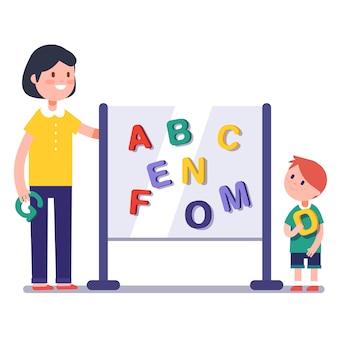 Bambino apprendimento abc in scuola materna con insegnante