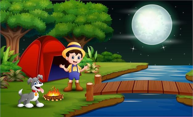 Bambino felice in campeggio con il suo animale domestico
