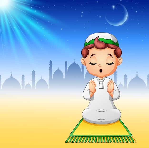Bambino musulmano che si siede sul tappeto di preghiera mentre pregava