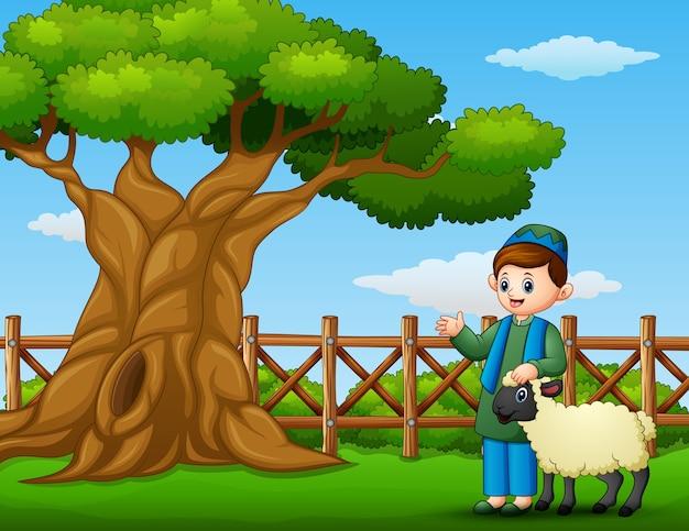 Bambino musulmano felice con una pecora al lato di un albero dentro il recinto
