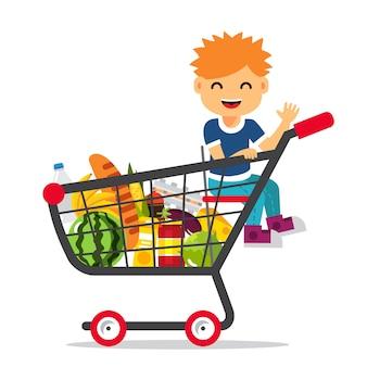 Bambino seduto in un carrello di shopping del supermercato