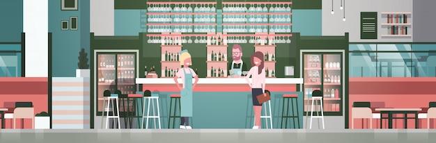 Bar stuff barista, cameriere e amministratore in piedi al bancone su bottiglie di alcol e bicchieri