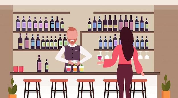 Barista in uniforme versando drink in bicchieri barista fare cocktail e servire donna client parlando bere vino al bancone bar ristorante moderno interno piatto orizzontale
