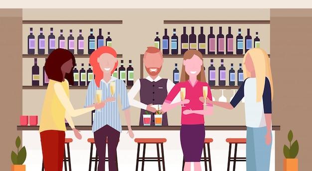 Barista versando drink in bicchieri barista fare cocktail e servire mix gara donne clienti che bevono champagne al bancone bar ristorante moderno interno piatto orizzontale ritratto