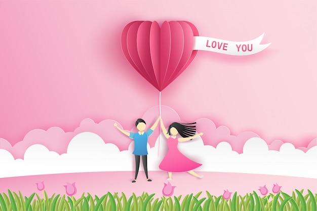 Bella coppia sul prato con origami palloncino rosa cuore e fiori a san valentino con testo ti amo.