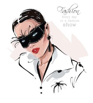 Bella giovane donna disegnata a mano nella maschera nera di carnevale con le piume. ragazza alla moda. look da donna alla moda.