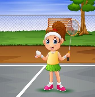 Bella ragazza che gioca a badminton alla corte